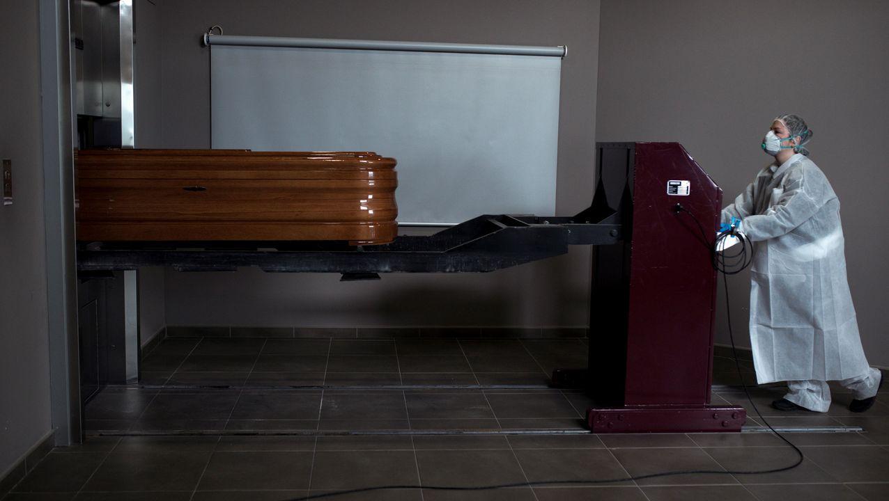 Una operaria transporta un ataúd con un fallecido por coronavirus para proceder a su incineración en el interior de la capilla del crematorio-tanatorio As Burgas, en Ourense