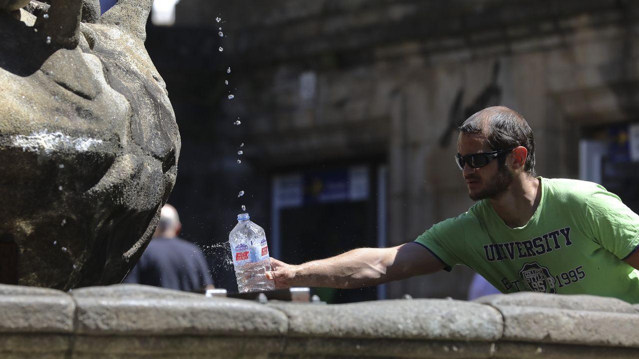 Un turista coge agua en una fuente de Compostela