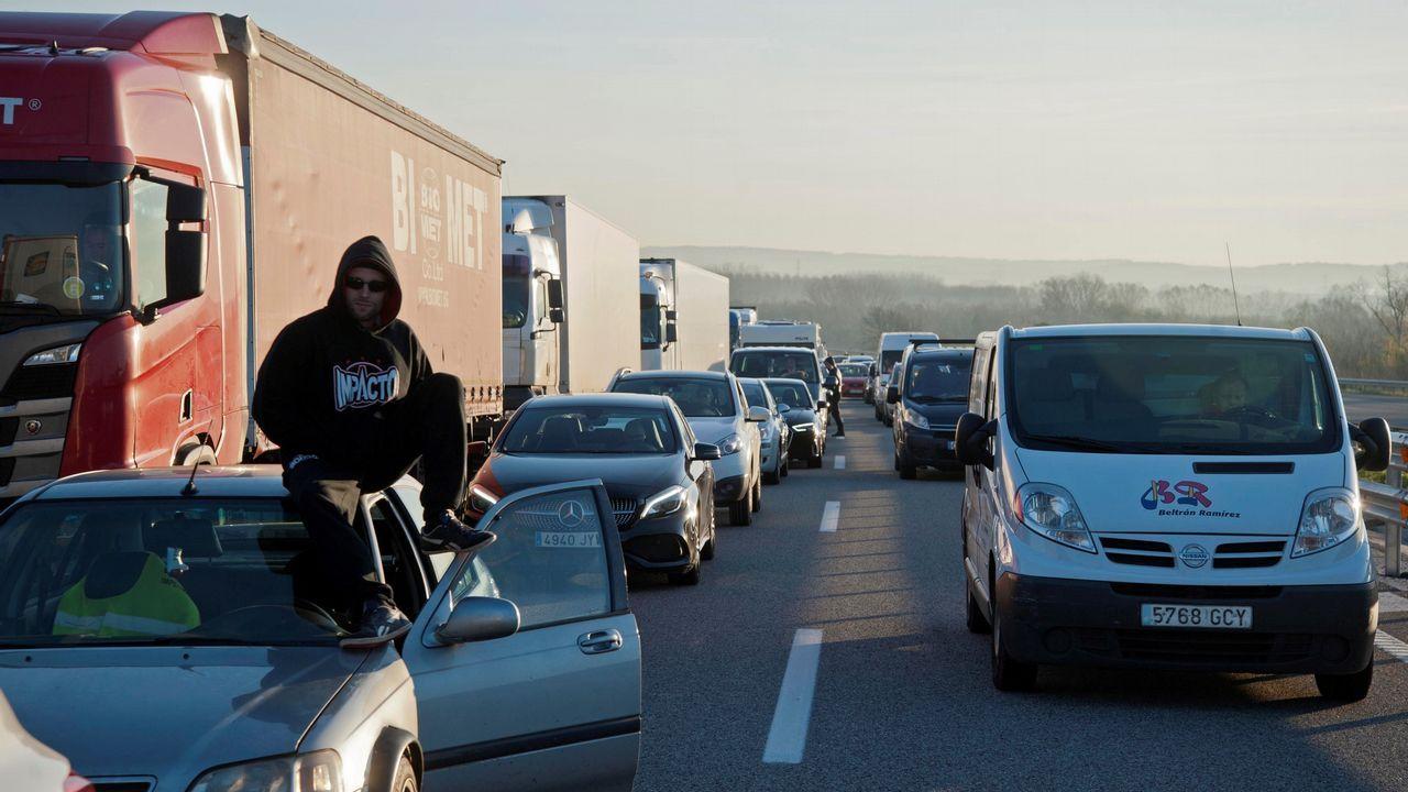 Varios conductores esperan fuera de sus vehículos durante la retención que ha provocado en la autopista AP-7 el corte que han realizado grupos independentistas