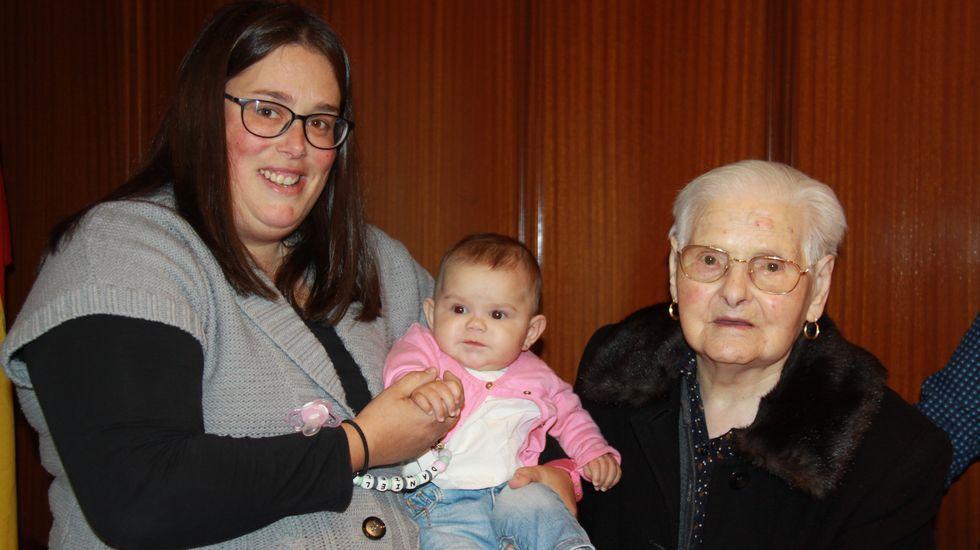 Daniela, en brazos de su madre, es la vecina más joven de Río. Isolina es la de mayor edad