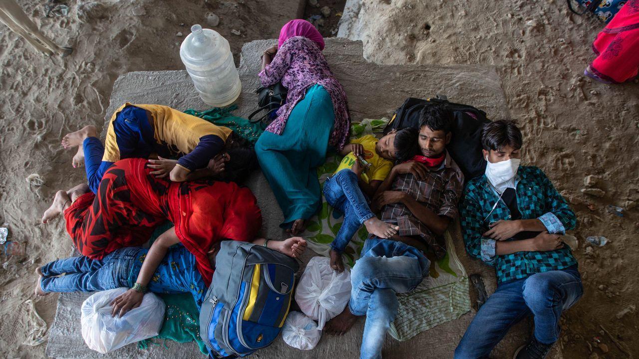 Trabajadores inmigrantes duermen fuera de sus casas en Nueva Delhi, India, tras denegarles el acceso de vuelta debido al cierre por cuarentena