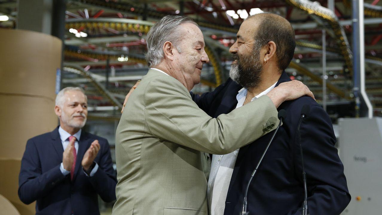 Santiago Rey abraza a Jorge Casanova, presidente del comité de empresa ante Lois Blanco, director general de la Corporación Voz