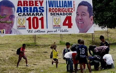 Un grupo de niños juega junto a vallas publicitarias en la ciudad de Buenaventura.