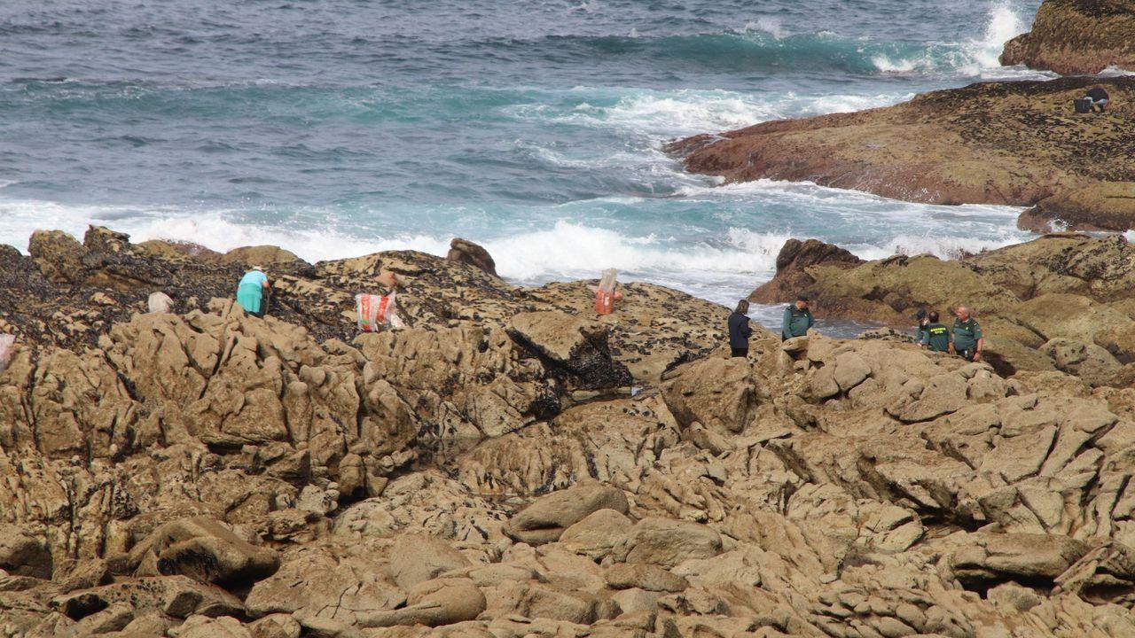 Guardias civiles con bateeiros que recolectaban mejila este viernes en la costa de Oia, en Pontevedra
