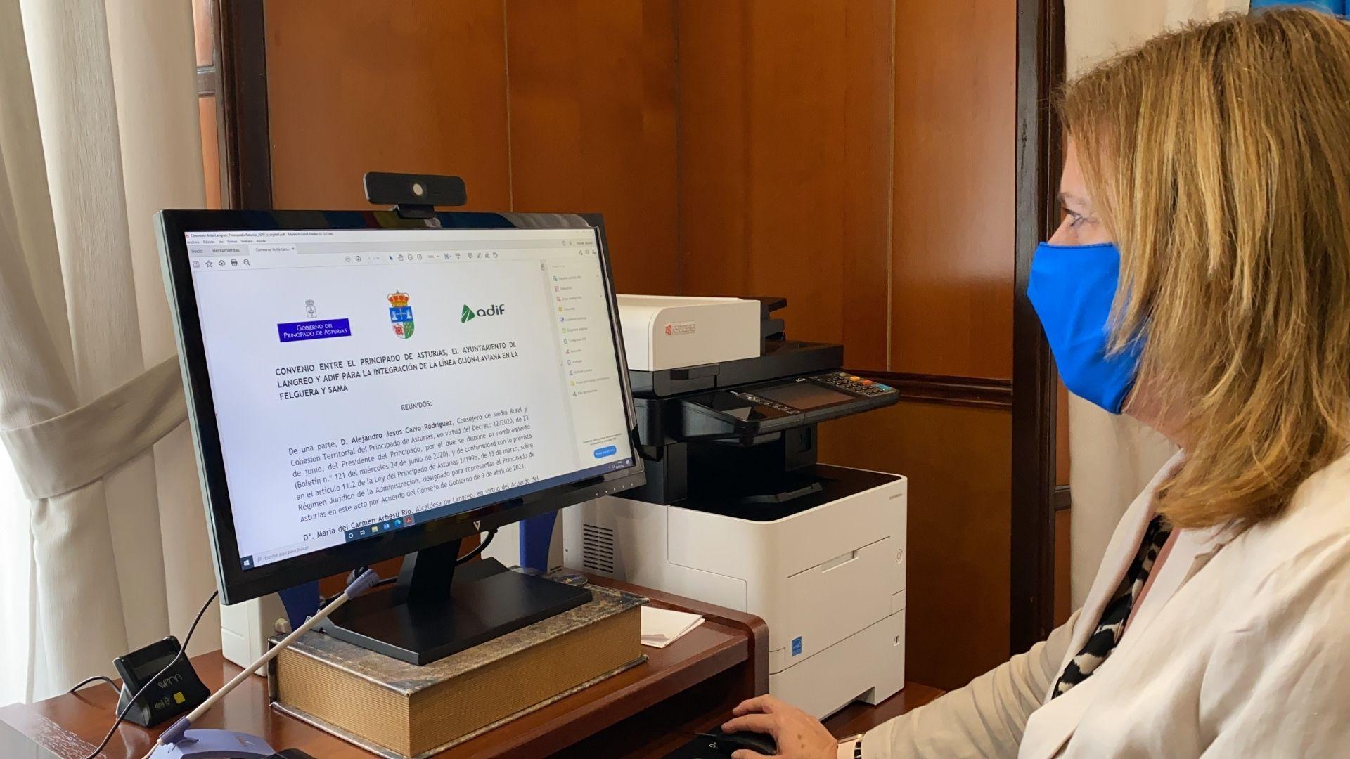 La alcaldesa de Langreo, Carmen Arbesú, firma de manera electrónica el convenio entre ADIF, el Principado y el Ayuntamiento para la ejecución de las obras pendientes del soterramiento de las vías de la antigua Feve entre Sama y La Felguera