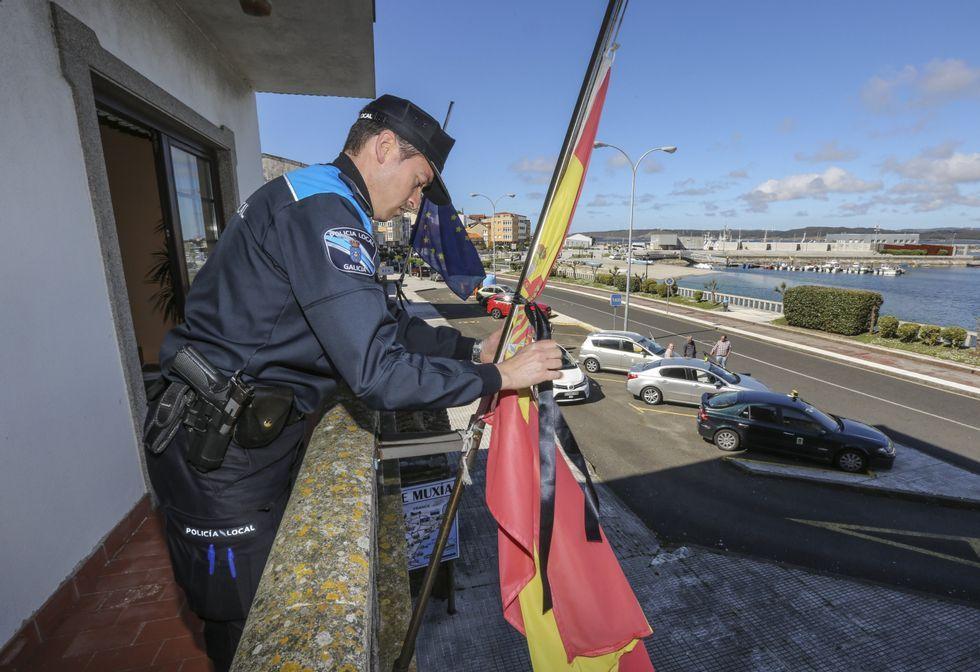 Un policía local coloca un crespón negro en la bandera española, que quedó izada a media asta.