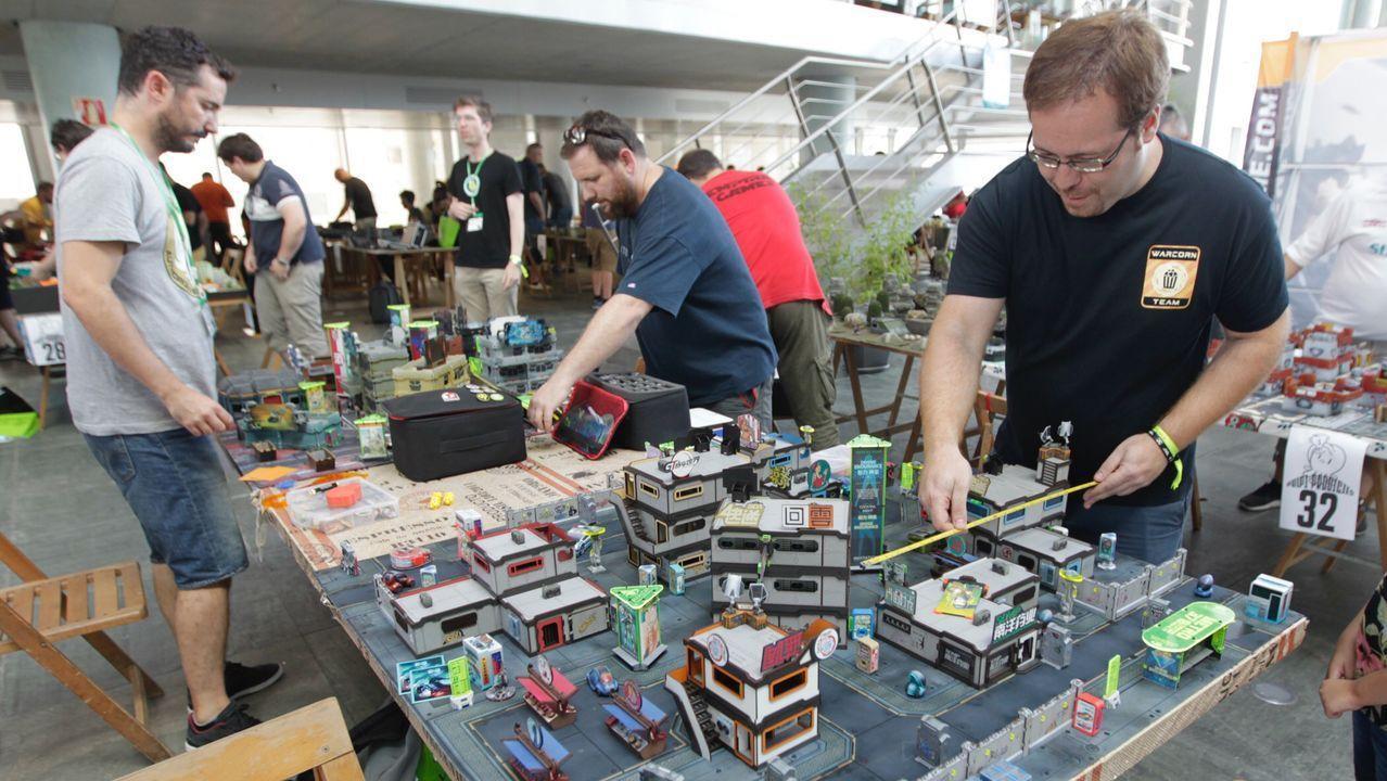 Los jugadores organizan sus piezas en una partida de Infinity.