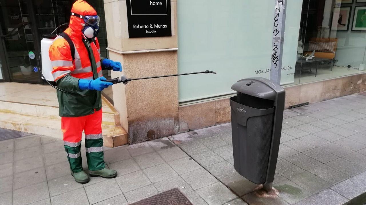 Un trabajador de Emulsa desinfecta una papelera, en una calle de Gijón