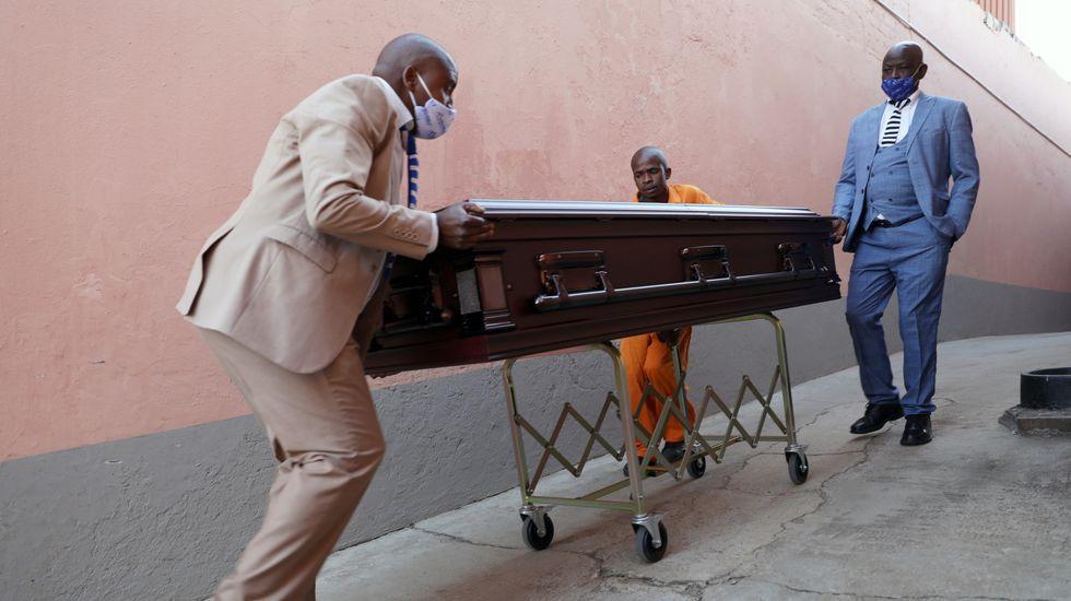 Enterradores se preparan para transportar un cuerpo antes del servicio funerario en Soweto, Sudáfrica