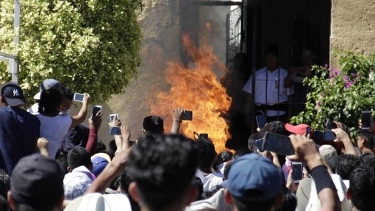 La multitud grabando con sus teléfonos cómo se queman vivos los dos hombres inocentes