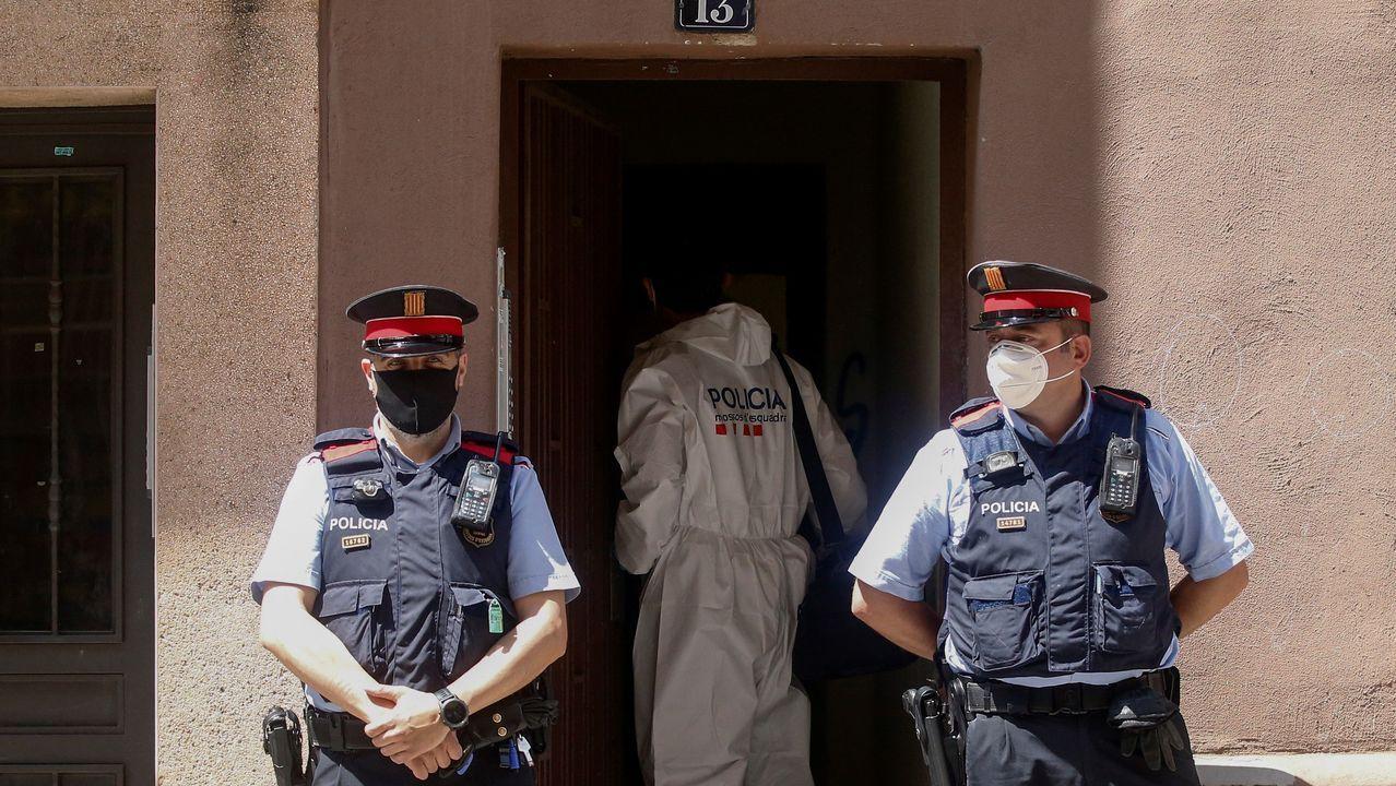 Dos Mossos d'Esquadra vigilan la entrada al piso donde se cometió el crimen.