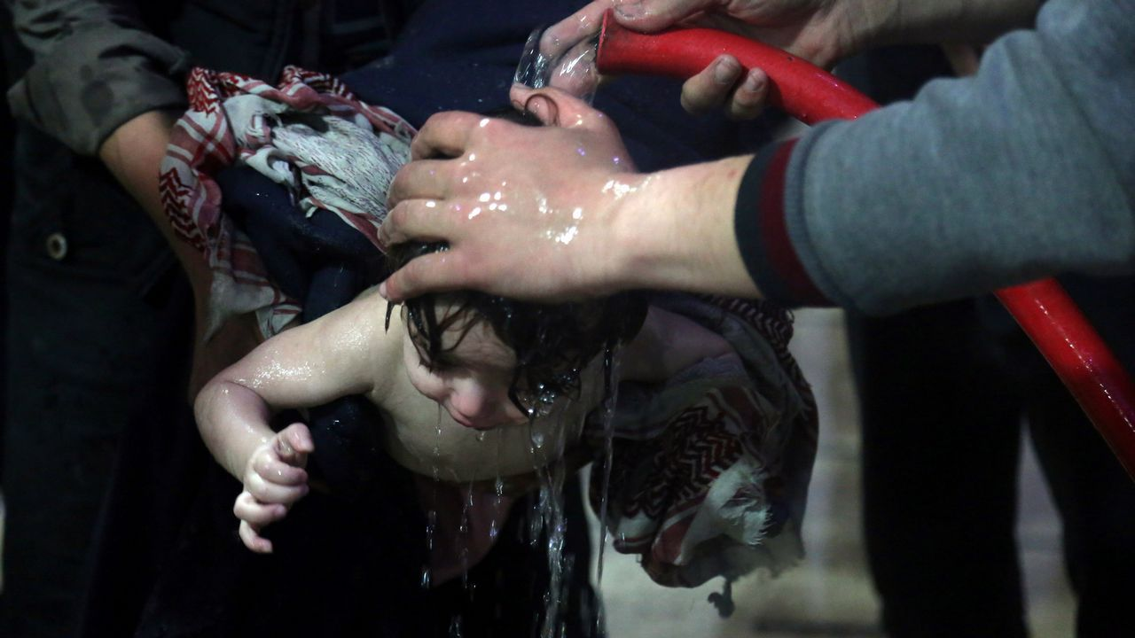 Las imágenes delataquede los aliadosa Siria.Un grupo de sanitarios del hospital de Duma lavan con agua a un bebé afectado tras el ataque de sábado con gas cloro