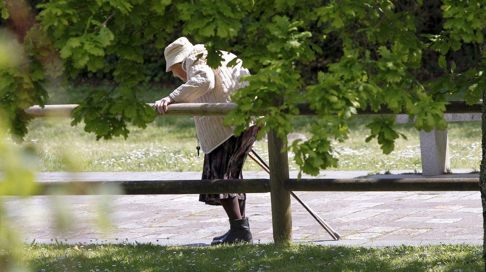 Una anciana pasea por un paseo fluvial