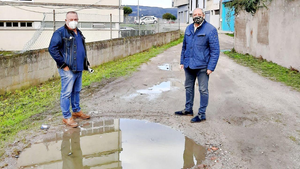 Los populares Soto y Rodríguez, ante una de las fochancas del vial que piden pavimentar