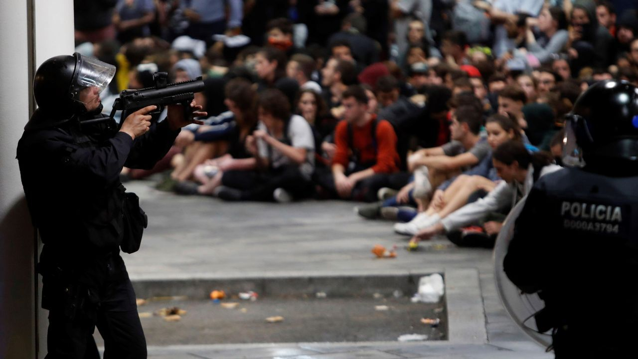Policías antidisturbios ante los manifestantes que se concentraron el lunes en el aeropuerto de El Prat