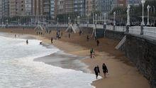 Varias personas caminan por la playa de San Lorenzo de Gijón