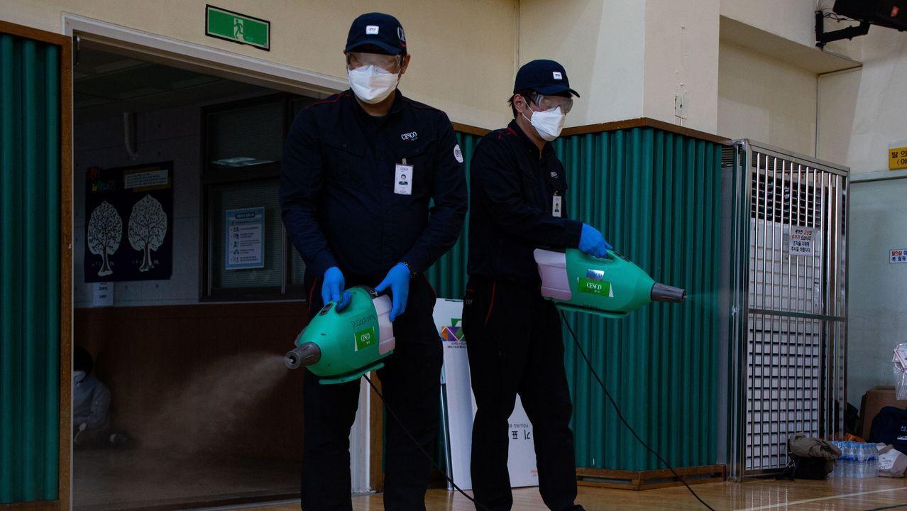 Trabajadores desinfectan un colegio electoral para la celebración de las elecciones generales en Seul, Corea