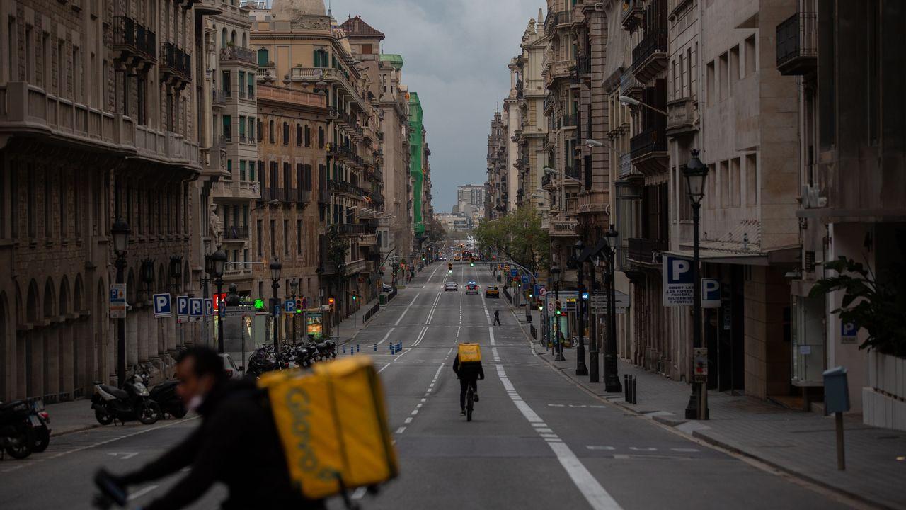 Dos trabajadores en bicicleta por una calle de Barcelona