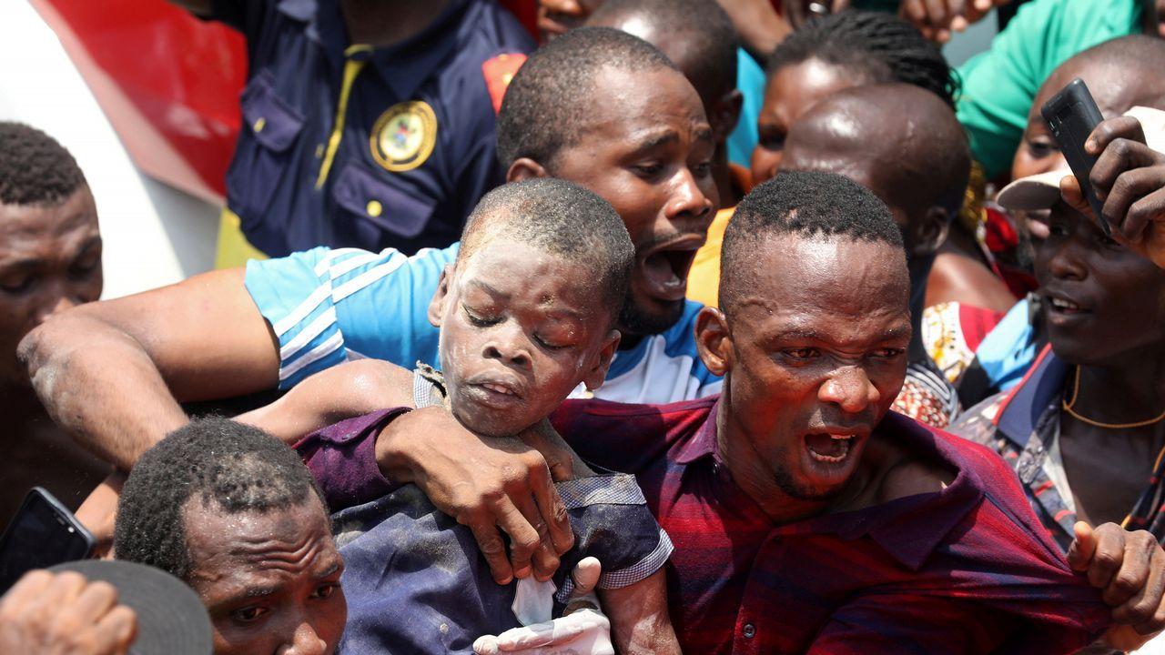 Un hombre lleva en brazos a uno de los niños rescatados de la escuela tras el desplome del edificio