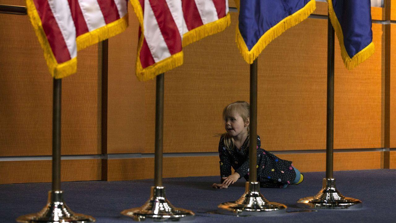 Una niña juega detrás de una serie de banderas en la Casa Blanca