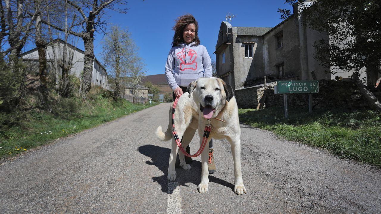 Eva y su perro Firuláis, junto a la casa familiar en la frontera gallega en la que se instaló