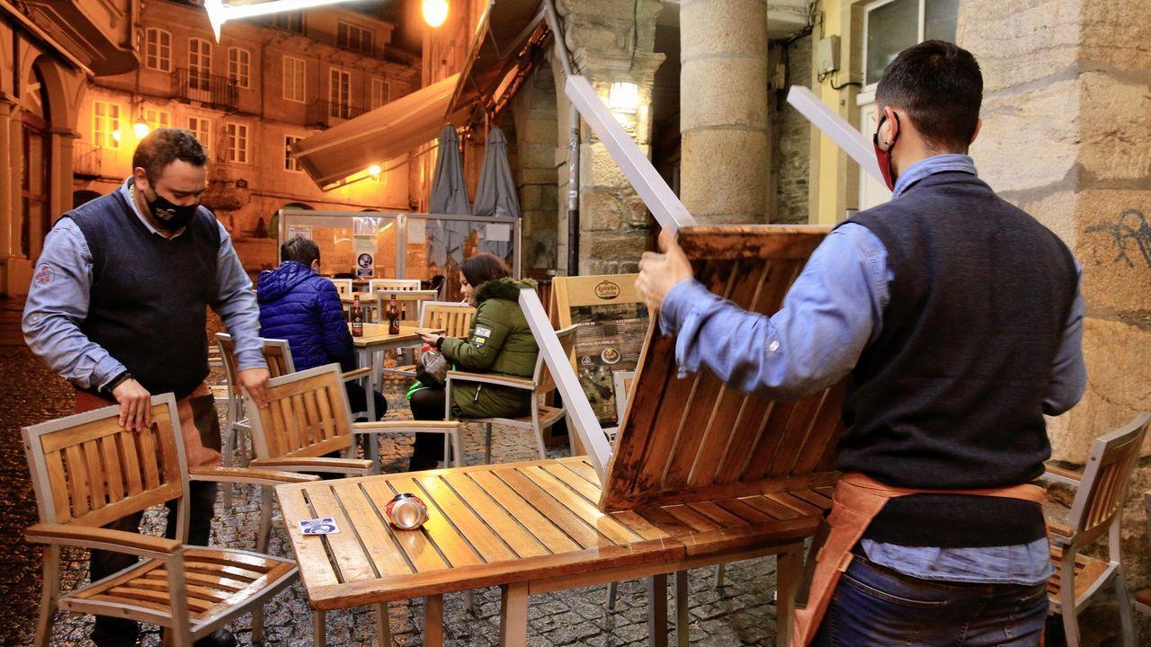 El toque de queda adelantó los cierres a las 23.00. Hosteleros recogiendo las mesas en Lugo
