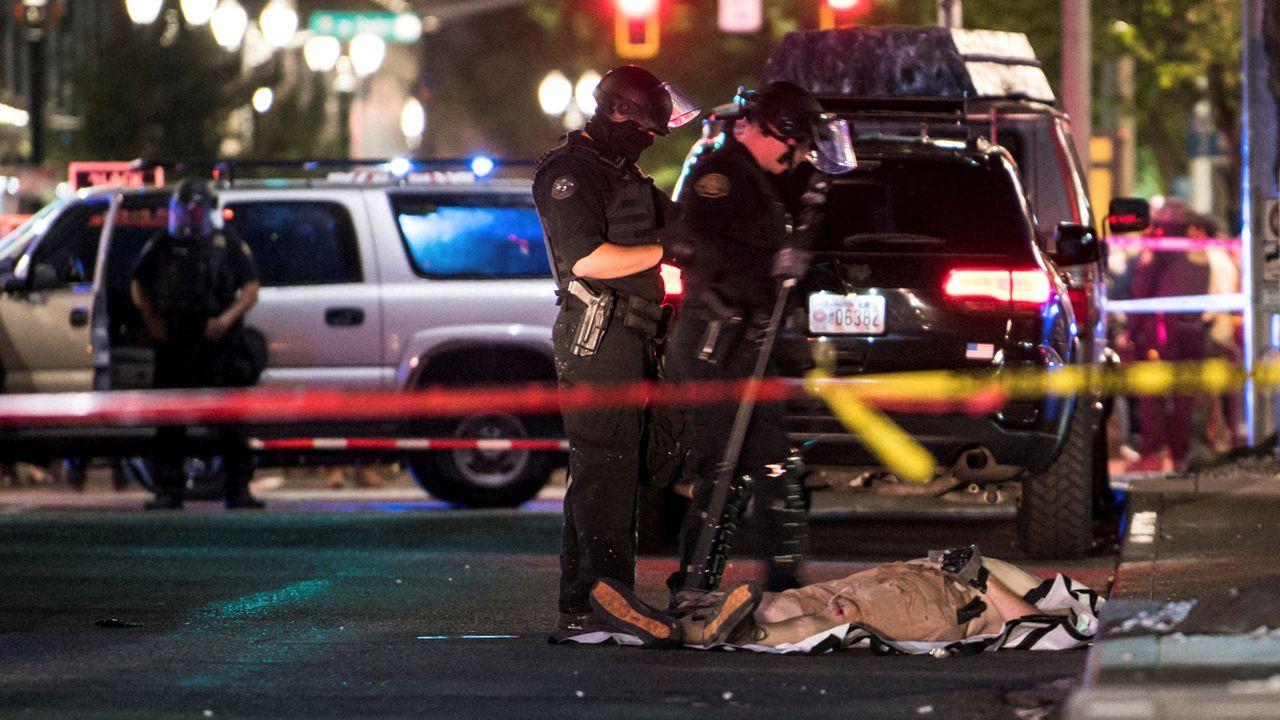 Policias observan el cuerpo del ultraderechista muerto a tiros la noche del sábado al domingo en Portland