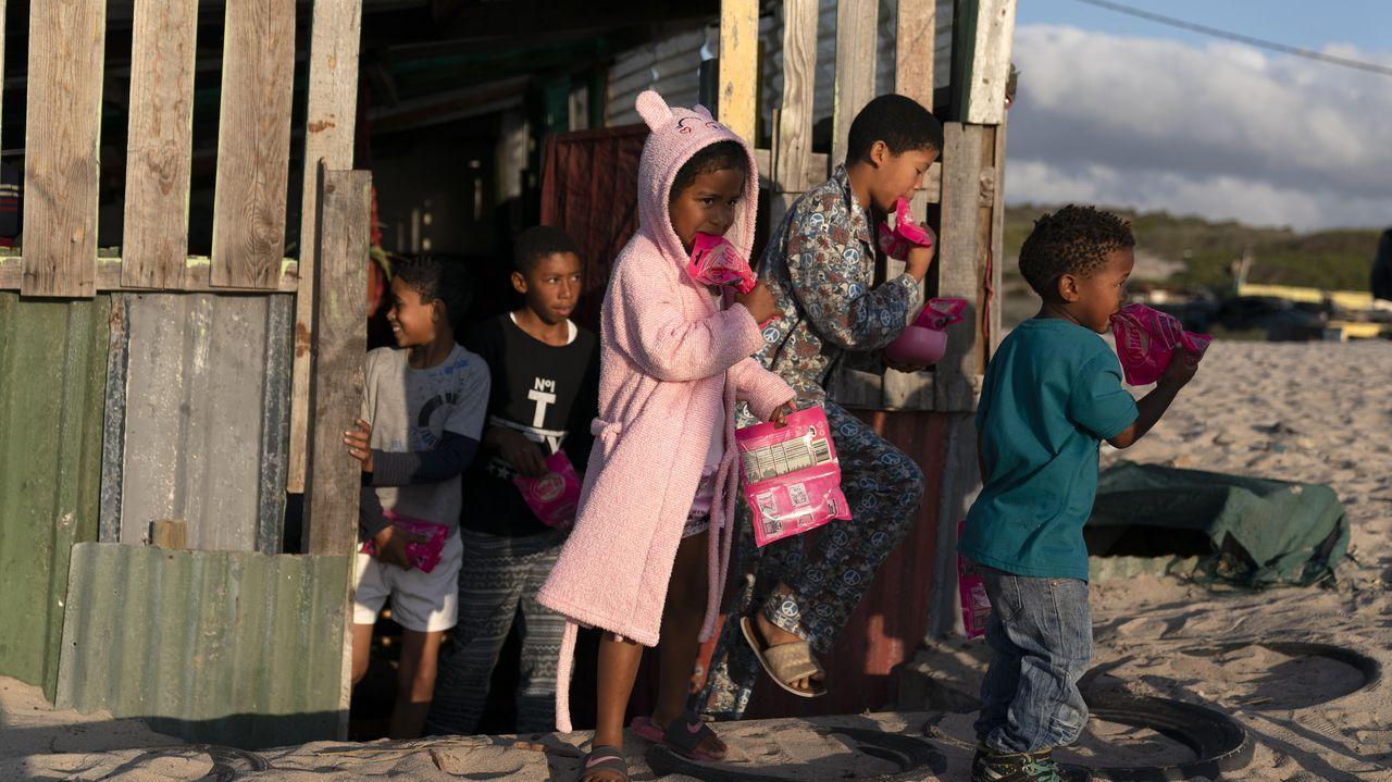 Un grupo de niños sudafricanos tras recibir un paquete de alimentos. Sudáfrica es el país africano mas castigado por la pandemia del covid-19