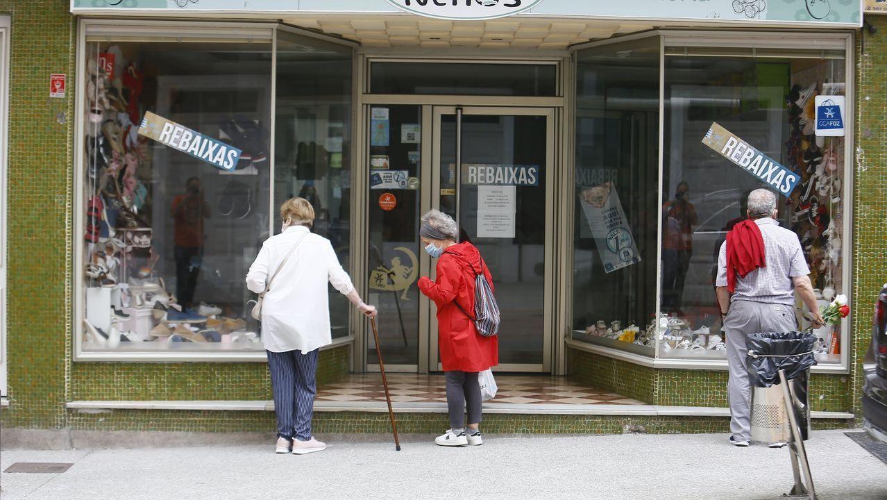 Gente ante un comercio de Foz, dias atrás
