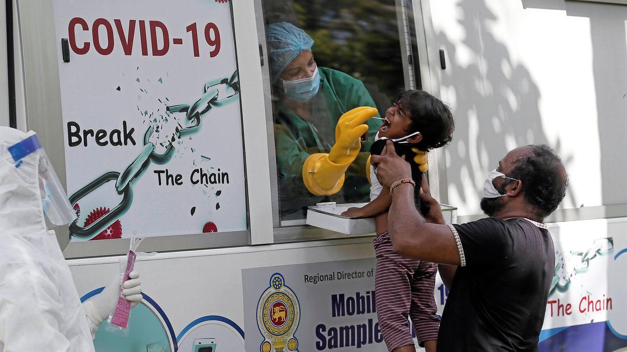 Una niña reacciona cuando un funcionario de salud usa un hisopo para obtener la muestra en una aldea durante el toque de queda, en Colombo, Sri Lanka