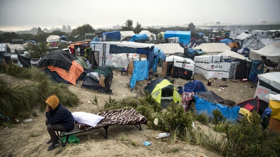 Un inmigrante fala polo móbil durante a evacuación do campamento coñecido como a Xungla de Calais