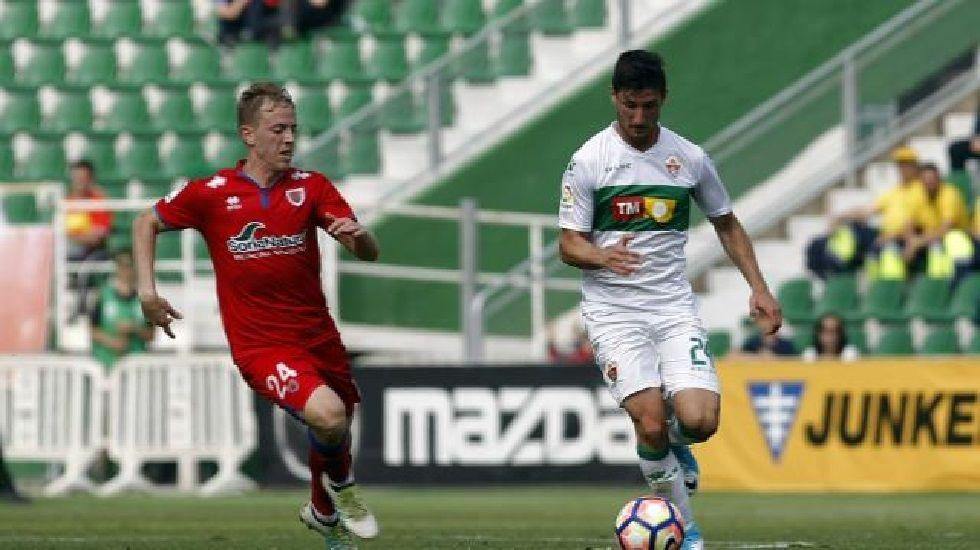 Borja Valle conduce un balón en un partido con el Elche