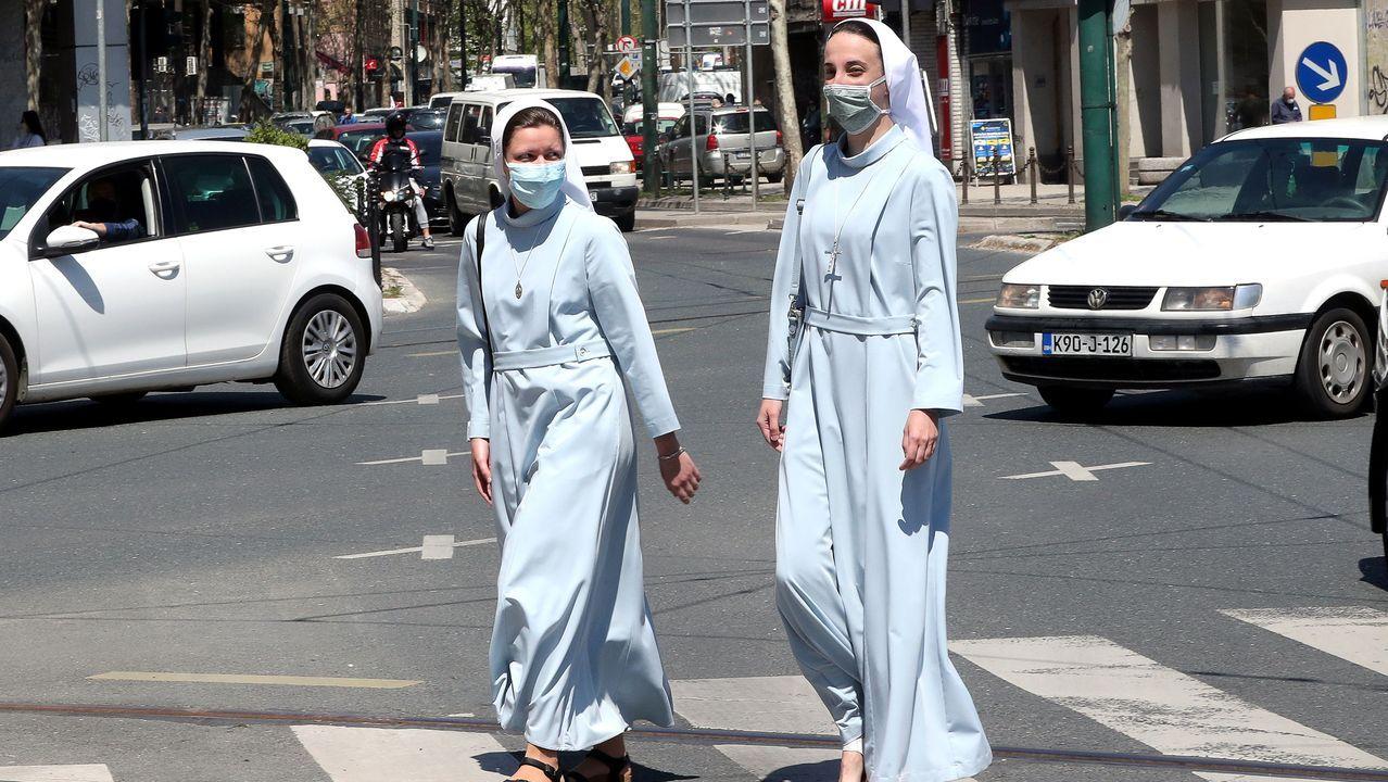 Dos monjas camina por Sarajevo ataviadas con mascarillas
