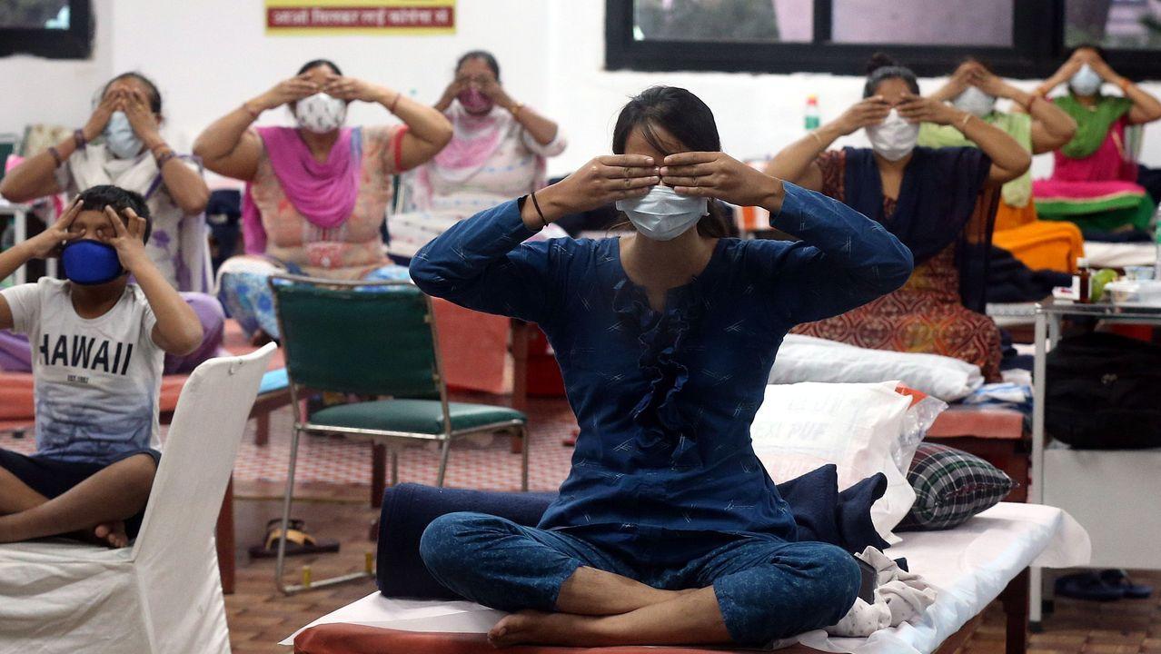 Los pacientes infectados con Covid-19 realizan yoga en el centro de atención COVID 19 y en la instalación de la sala de aislamiento que se adjunta a un hospital en Nueva Delhi, India