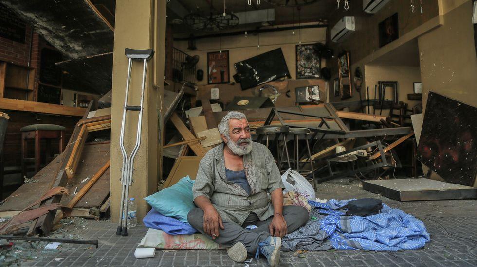 Un hombre se sienta en la acera enfrente de un bar destruido por la explosión