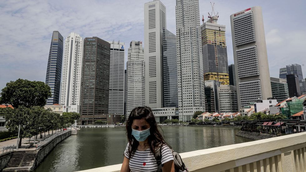 Una mujer camina por el distrito financiero de Singapur
