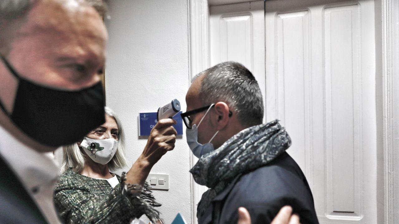 El socialista Rafael Villarino pasa al lado del popular Jesús Vázquez, al que estan tomando la temperatura para acceder al pleno municipal