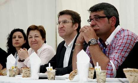 El presidente de la Xunta, entre Pilar Farjas y Antonio Devesa, ayer en la comida de Muxía.