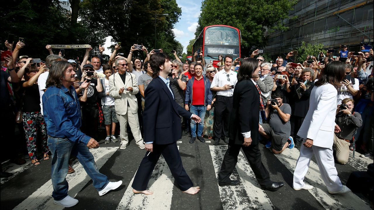 Una banda tributo de los Beatles cruza el paso de cebra de Abbey Road