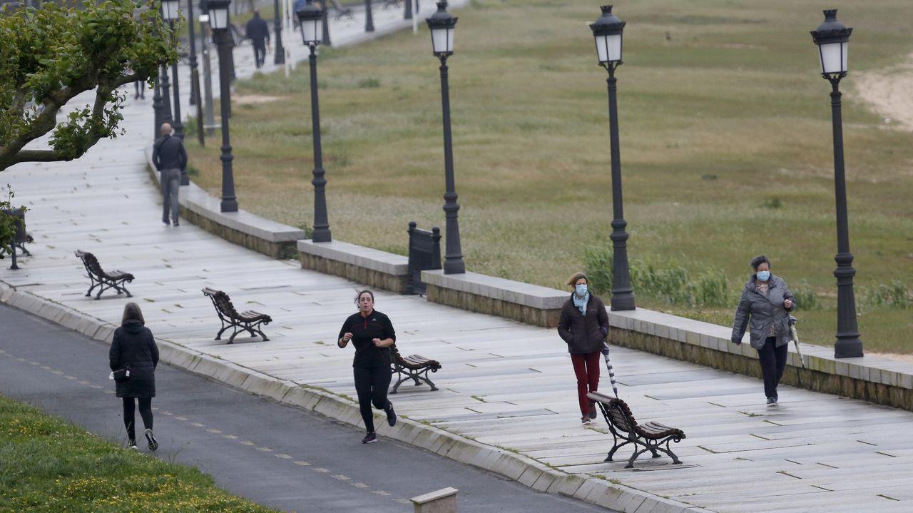 Deportistas y viandantes en el paseo de Coroso en Ribeira