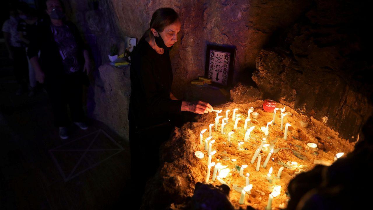 Una mujer, con la mascarilla apartada, enciende velas en una iglesia de Nazaret