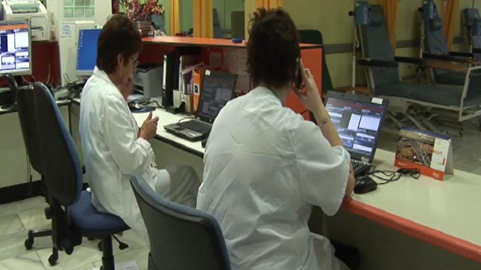 Unos turistas consultan un plano de Oviedo en la calle Uría.Administrativas en un centro de salud