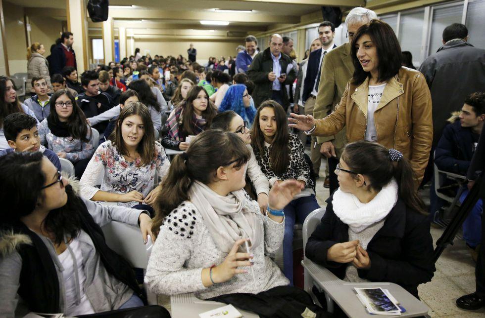 La conselleira, de pie, saludando a los estudiantes a su entrada al salón de actos del instituto.