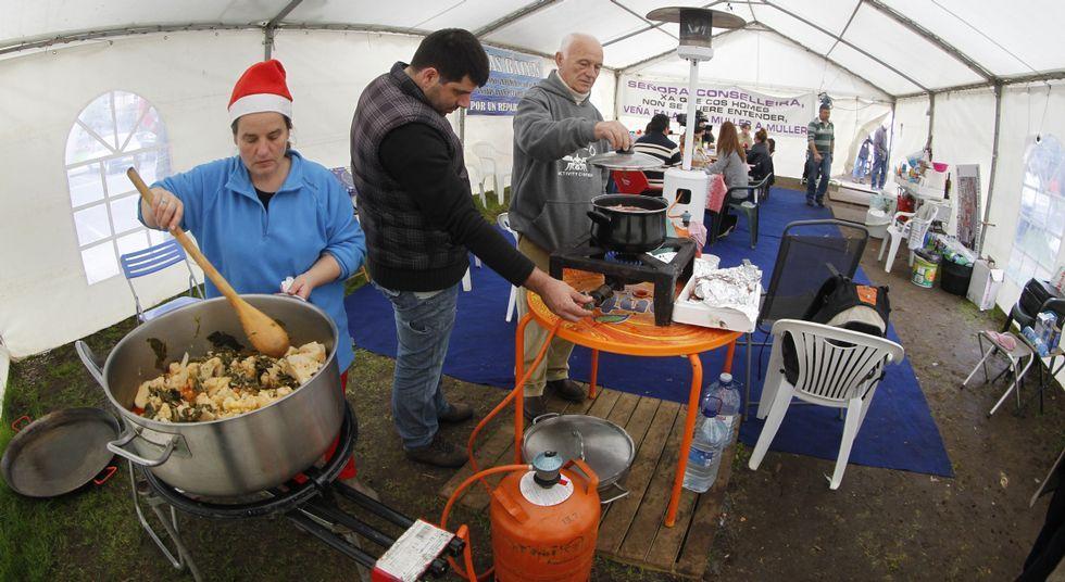 Una Navidad en tienda de campaña.Oubiña, de Cambados, controla el fuego de la olla en la que Barizo, de Malpica, cocina langostinos.