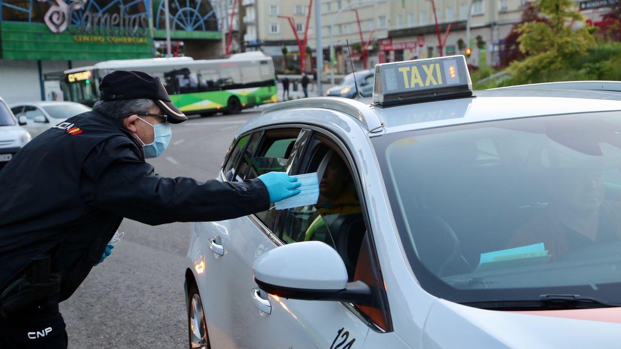 Policía Nacional, Local y Autonómica reparten mascarillas a transeúntes y conductores en la plaza de América de Vigo