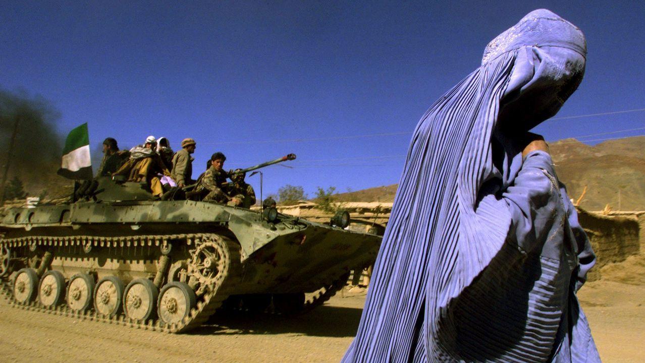 La sorpresa de unmilitar de la Brilat recien llegado de Mali a su hijode 8 años.Una mujer vestida con burka camina junto a un tanque con una bandera afgana en Kabul