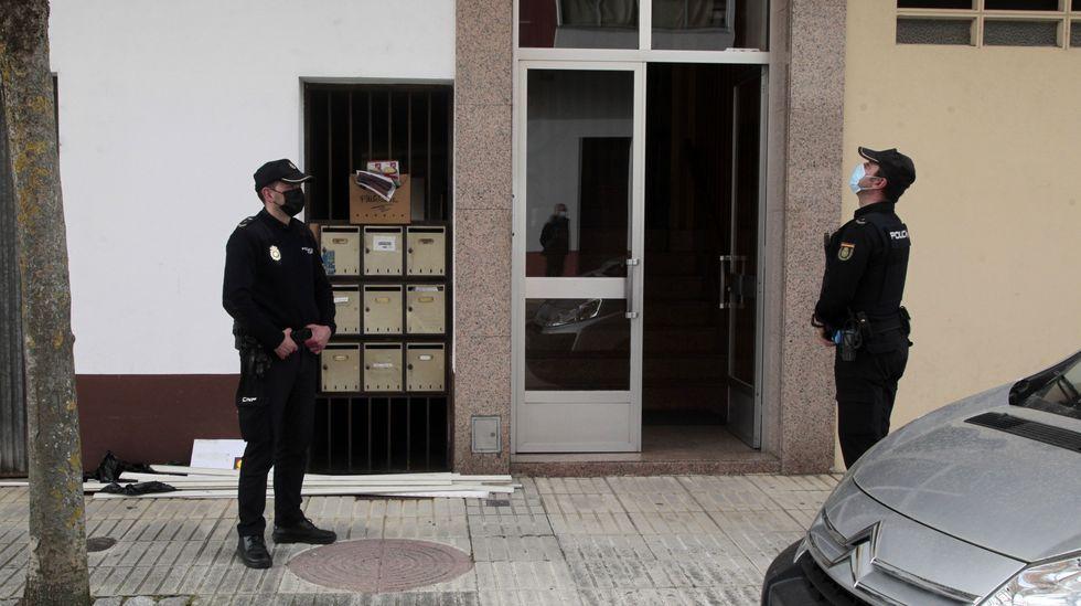 Las fotos del incendio de Marcelle, en Monforte.Dos policías, frente al portal del edificio de Monforte en el que vivía el hombre encontrado muerto