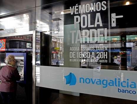 Una mujer opera en un cajero en una oficina de NCG en A Coruña.