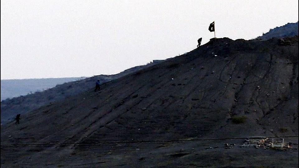 Fotografía hecha desde Turquía que muestra a miembros del Estado Islámico plantando su bandera negra al este de Kobani