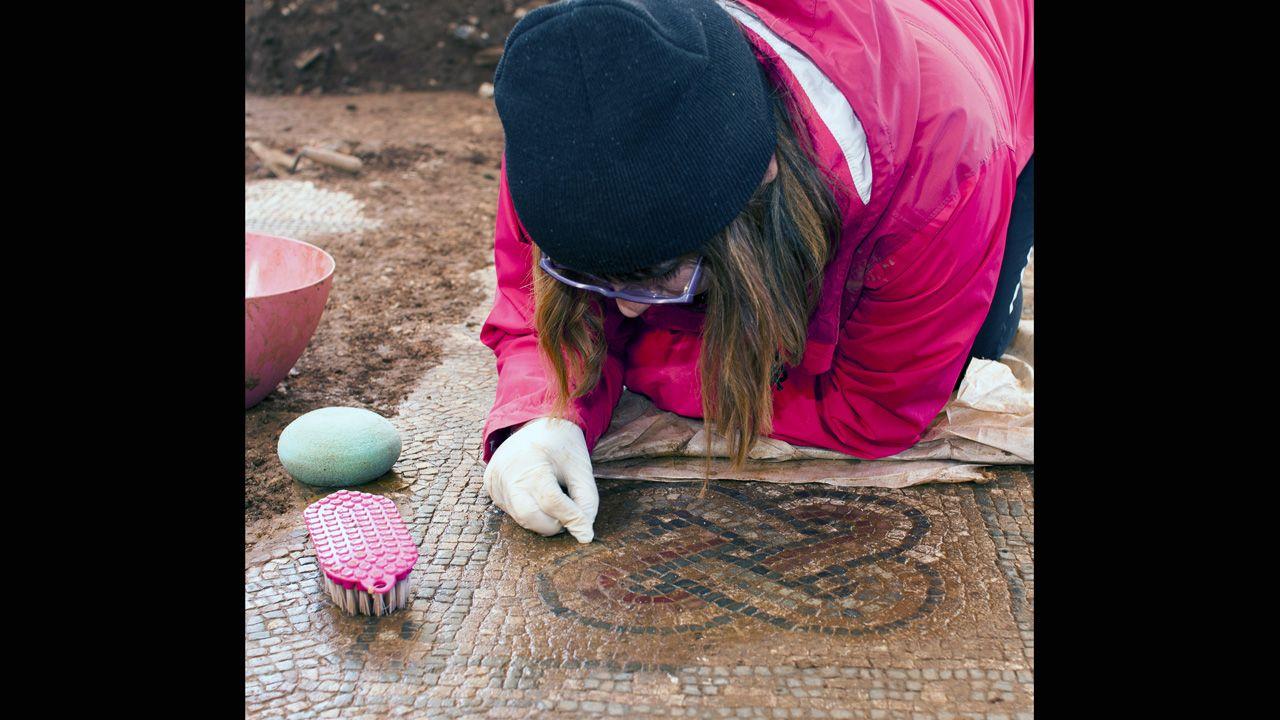 María Rodríguez retira minuciosamente la concreción adherida a las teselas del mosaico de casa romana